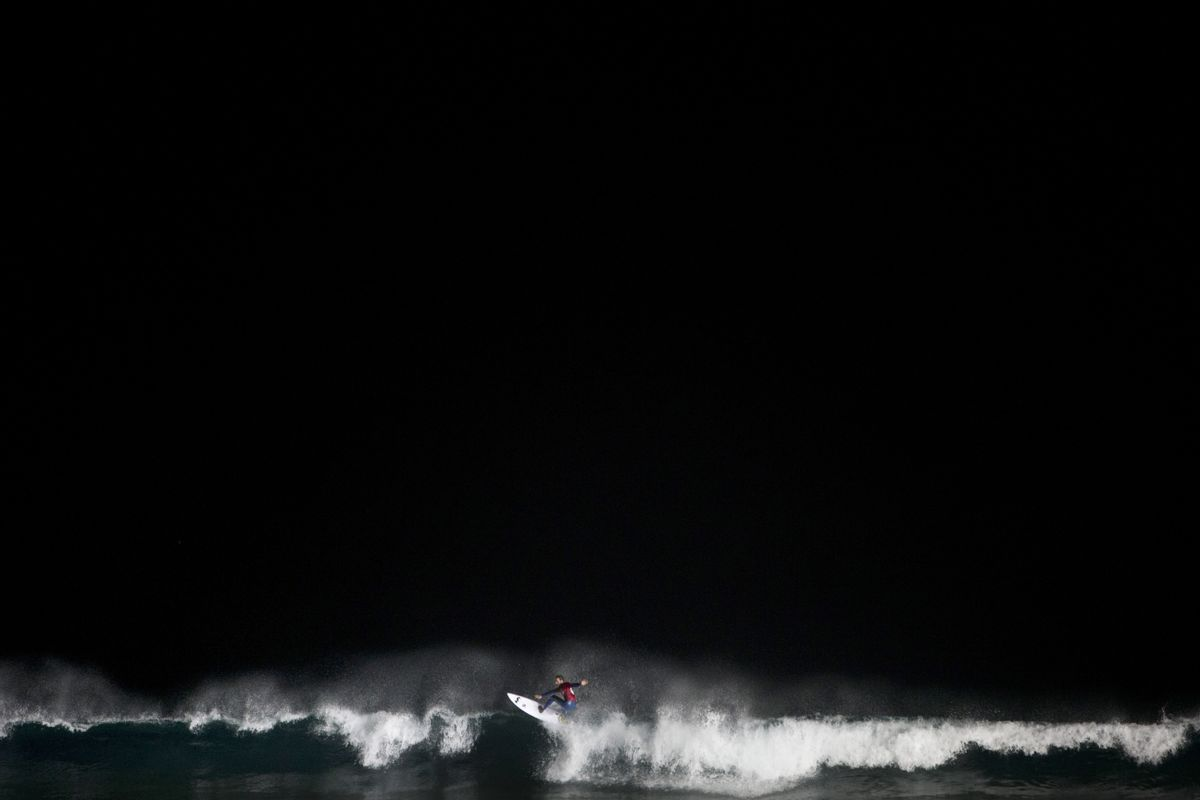AP10ThingsToSee - A surfer catches a wave during a night surfing competition in the Mediterranean sea in Ashdod, southern Israel on Wednesday, Feb. 4, 2015. About 40 surfers participated in the competition which started Wednesday after sundown. (AP Photo/Oded Balilty) (AP)