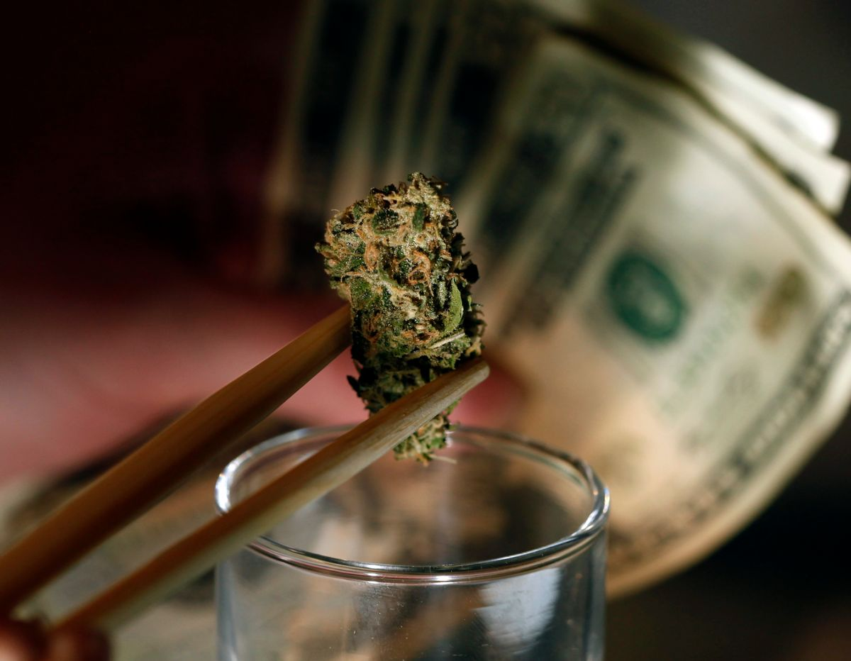 In this Sept. 18, 2012, file photo a caregiver picks out a marijuana bud for a patient at a marijuana dispensary in Denver.    (AP/Ed Andrieski)