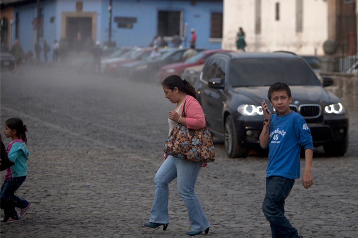 People cross a street covered with ash from the eruption of the Fuego Volcano at Antigua Guatemala, Saturday, Feb. 7, 2015.        (AP/Moises Castillo)