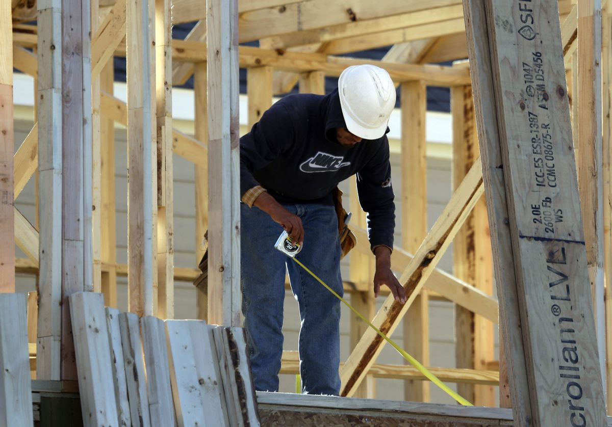In this Dec. 15, 2014 photo, a worker measures before cutting while working on the framing of a house under construction in Coppell, Texas. The Commerce Department reports on U.S. home construction in January on Wednesday, Feb. 18, 2015. (AP Photo/LM Otero) (AP)