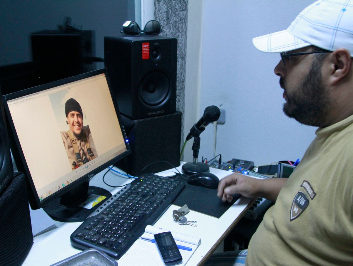 """In this Dec. 4, 2014 photo, Mehdi """"DJ Costa"""" Akkari, a Tunisian rapper, looks at an image of his brother Youssef, who fought with extremists in Syria and was killed by a U.S. airstrike, in Tunis, Tunisia. While foreigners from across the world have joined the Islamic State militant group, some arrive in Iraq or Syria only to find day-to-day life much more austere and violent than they had expected. (AP Photo/Paul Schemm) (AP)"""