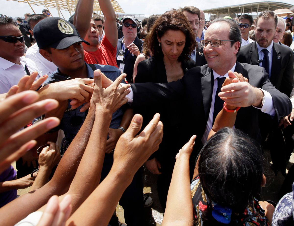 President Francois Hollande of France is greeted by the crowd during his visit to the  typhoon-ravaged Guiuan township, Eastern Samar province in central Philippines Friday, Feb. 27, 2015. Hollande's two-day state visit focuses on climate change.(AP Photo/Bullit Marquez) (Bullit Marquez)