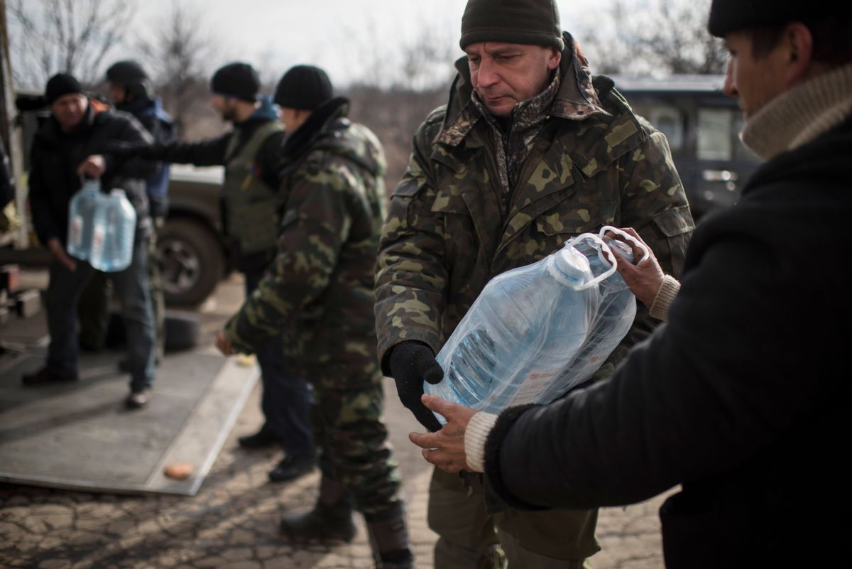 Ukrainian soldiers unload supplies near Debaltseve, eastern Ukraine, Sunday, Feb. 8, 2015. The government-held town of Debaltseve, a key railway junction, has been the epicenter of recent battles between Russian-backed separatists and Ukrainian government troops. For two weeks, the town has been pounded by intense shelling that knocked out power, heat and running water in the dead of winter. (AP Photo/Evgeniy Maloletka) (AP)