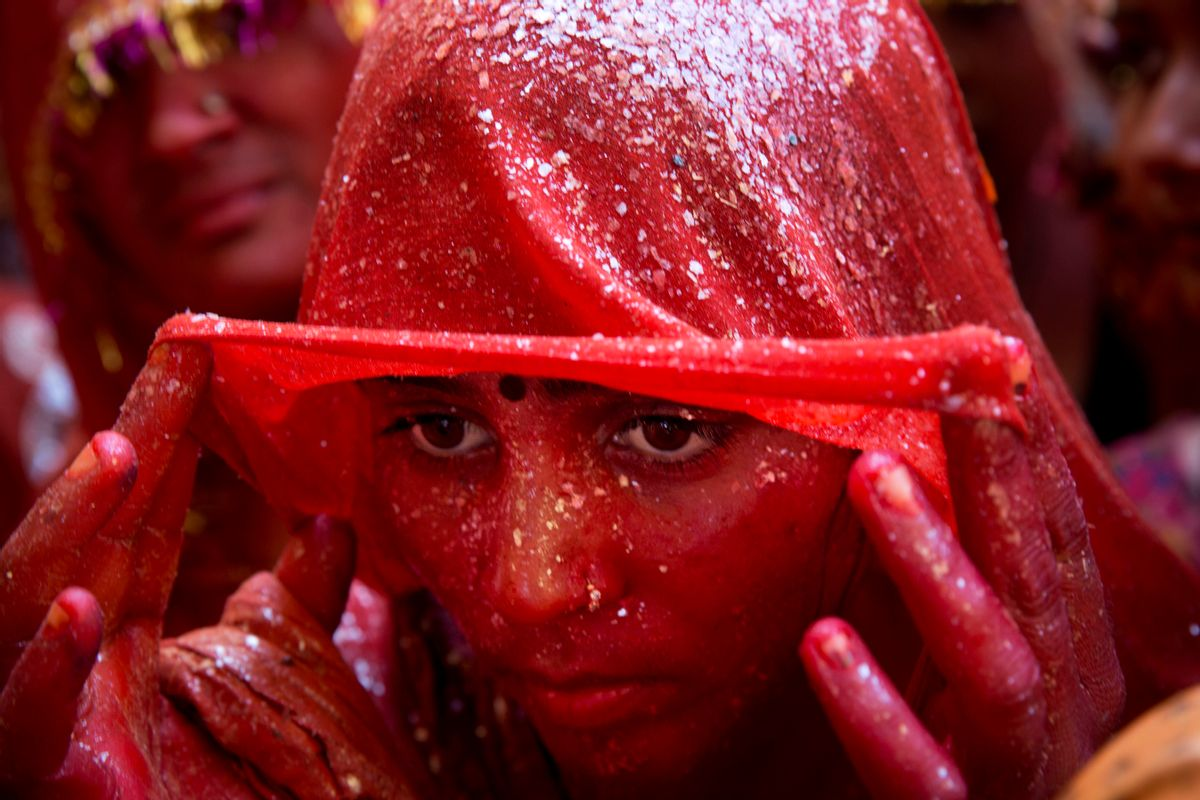 """AP10ThingsToSee - A Hindu woman devotee lifts her veil as she stands drenched in colored water during """"Huranga,"""" celebrated as part of Holi, the Hindu festival of colors, at the Baldev Temple in Dauji, 180 kilometers (113 miles) south of New Delhi, India, Saturday, March 7, 2015.   (AP Photo/Bernat Armangue) (AP)"""