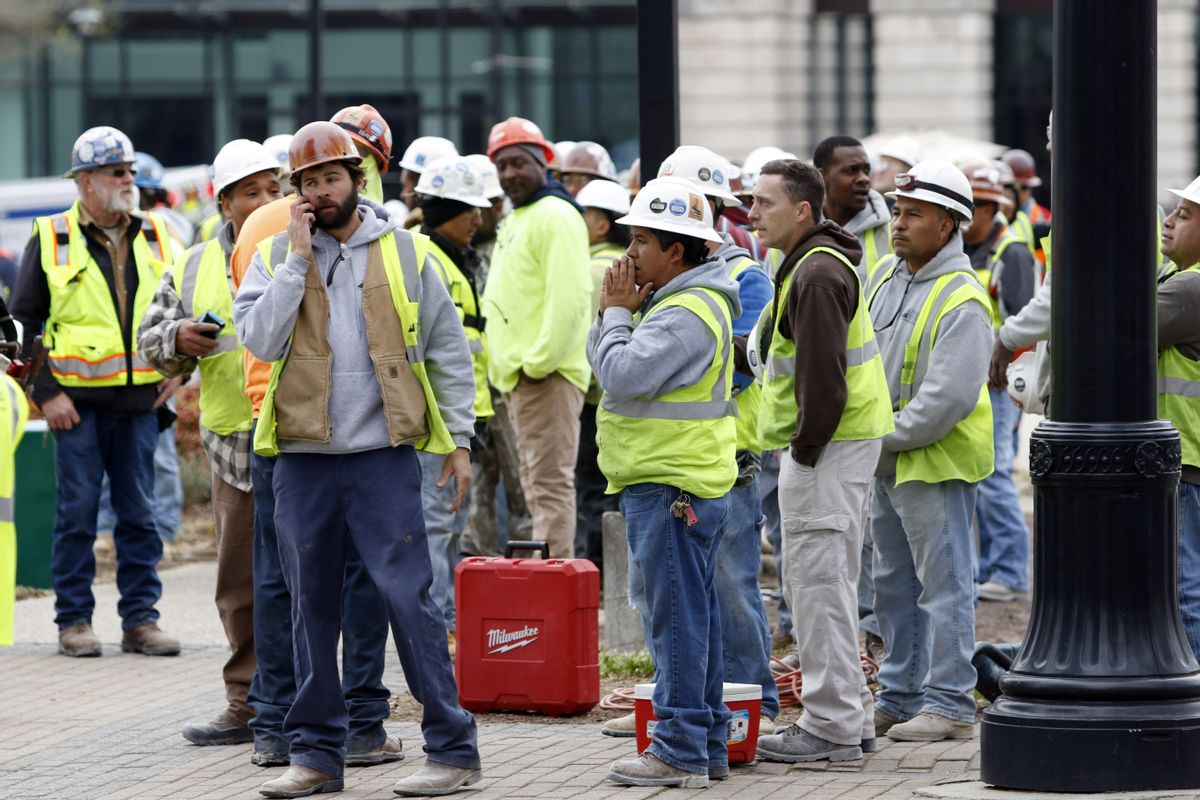 Construction workers gather outside the scene where a section of scaffolding collapsed at a high-rise construction project, killing three people and sending another to a hospital, Monday, March 23, 2015, in downtown Raleigh, N.C. (AP Photo/The News & Observer, Harry Lynch) (AP)
