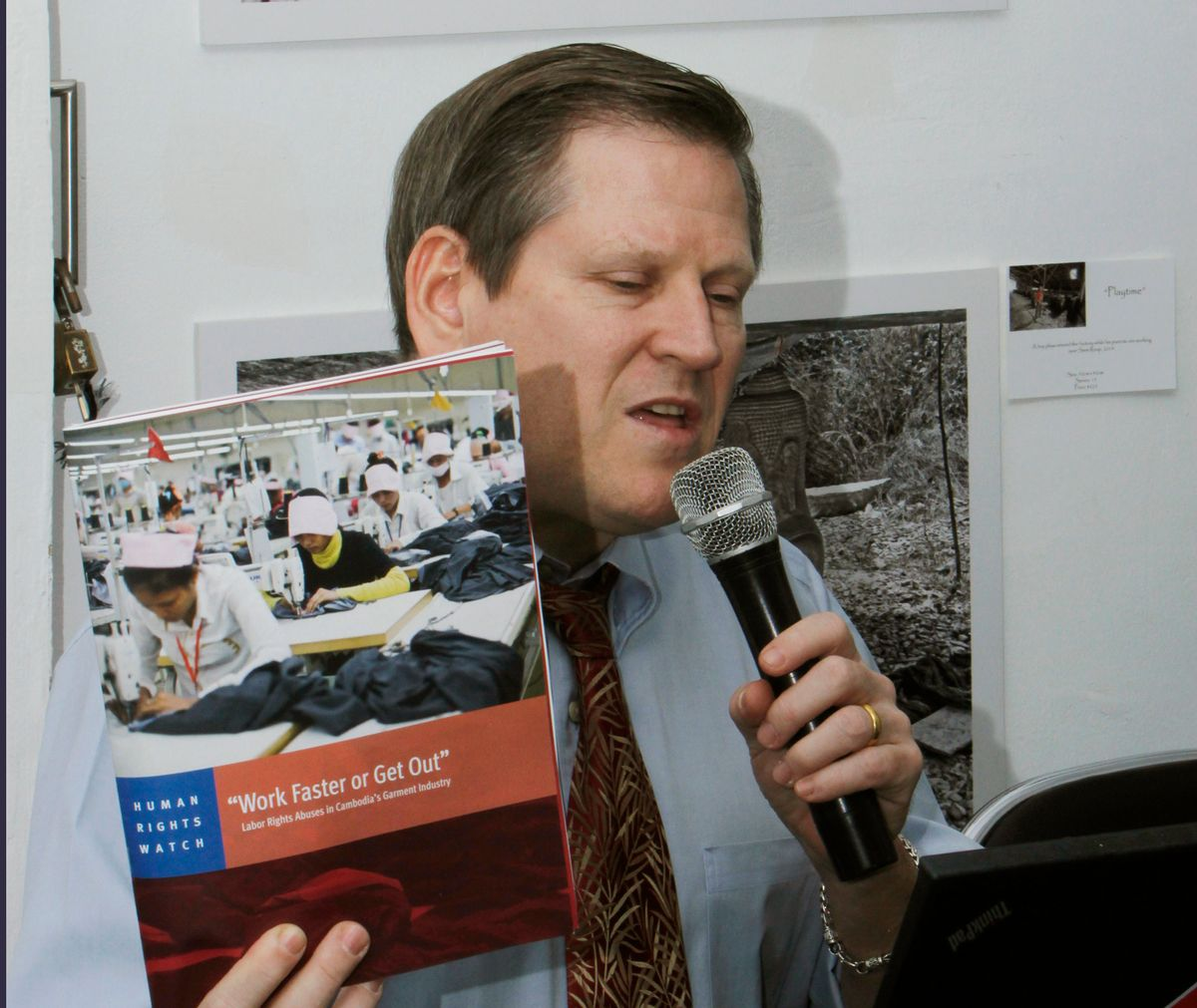 Phil Robertson, deputy director of Human Rights Watch's Asia division, speaks while showing its report during a press conference in Phnom Penh, Cambodia Thursday, March 12, 2015. Leading clothing retailers such as Gap and H&M need to help alleviate labor abuses at factories in Cambodia that manufacture their products, the New York-based human rights organization said. (AP Photo/Heng Sinith)  (Heng Sinith)