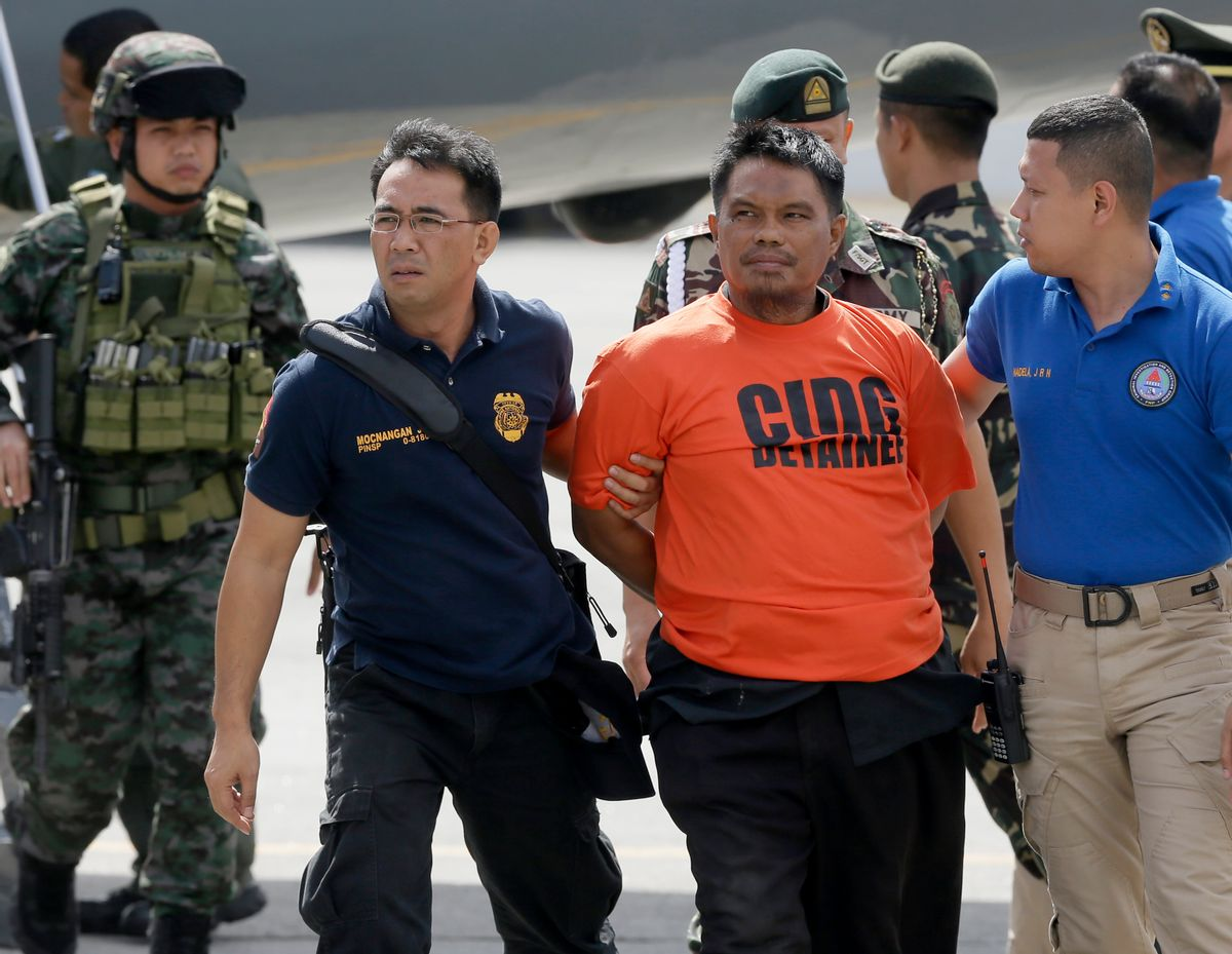 Army and police forces escort handcuffed Mohammad Ali Tambako,  the leader of a Muslim rebel group in the south who has been linked to bombings and a beheading and accused of protecting two terror suspects wanted by the United States, shortly upon arrival at Villamor Air Base at suburban Pasay city south of Manila, Philippines Monday, March 16, 2015. Tambako and five of his men were arrested late Sunday while the militants were traveling in a motorcycle sidecar taxi to a seaport in southern General Santos city.(AP Photo/Bullit Marquez) (AP)