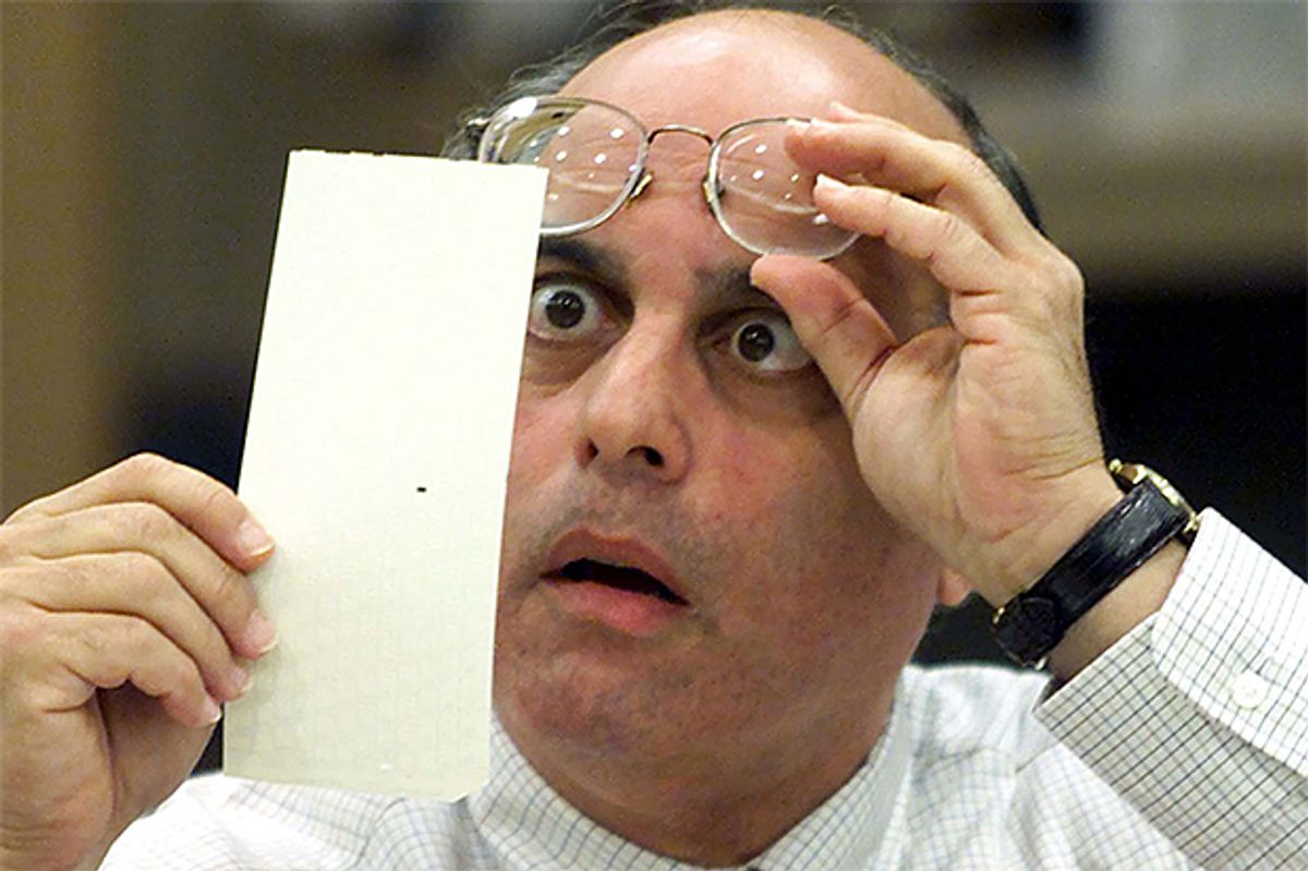 Broward County Canvassing Board member Judge Robert Rosenberg stares at a dimpled punchcard ballot November 23, 2000 during the recount of the 2000 presidential election.        (Reuters/Colin Braley)