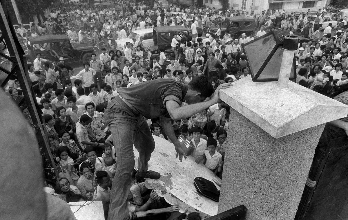 FILE - In this April 29, 1975, file photo, South Vietnamese civilians try to scale the 14-foot wall of the U.S. embassy in Saigon, trying to reach evacuation helicopters as the last Americans departed from Vietnam. More than two bitter decades of war in Vietnam ended with the last days of April 1975. (AP Photo/File) (AP)