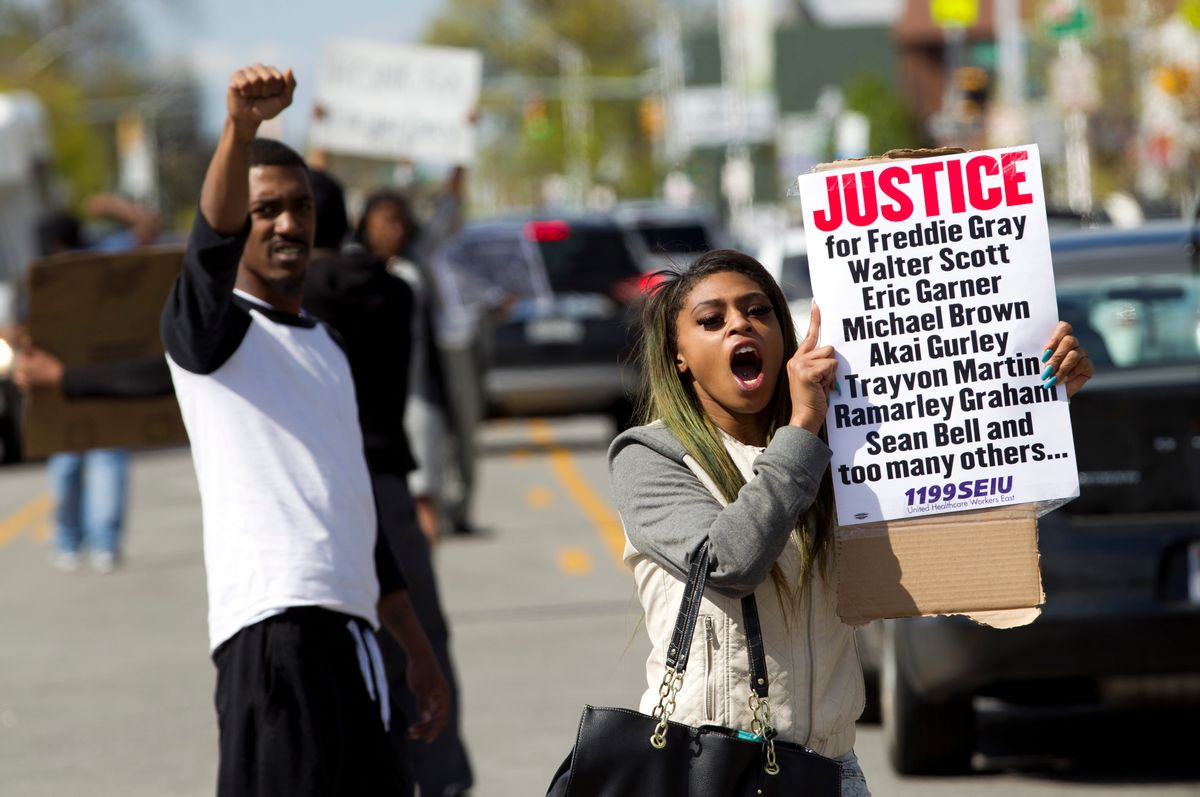 Caira Byrd hold support signs for Freddie Gray outside of Vaughn Greene Funeral Home, during his wake in Baltimore, Md., Sunday, April 26, 2015. Gray died from spinal injuries about a week after he was arrested and transported in a police van.  (AP/Jose Luis Magana)