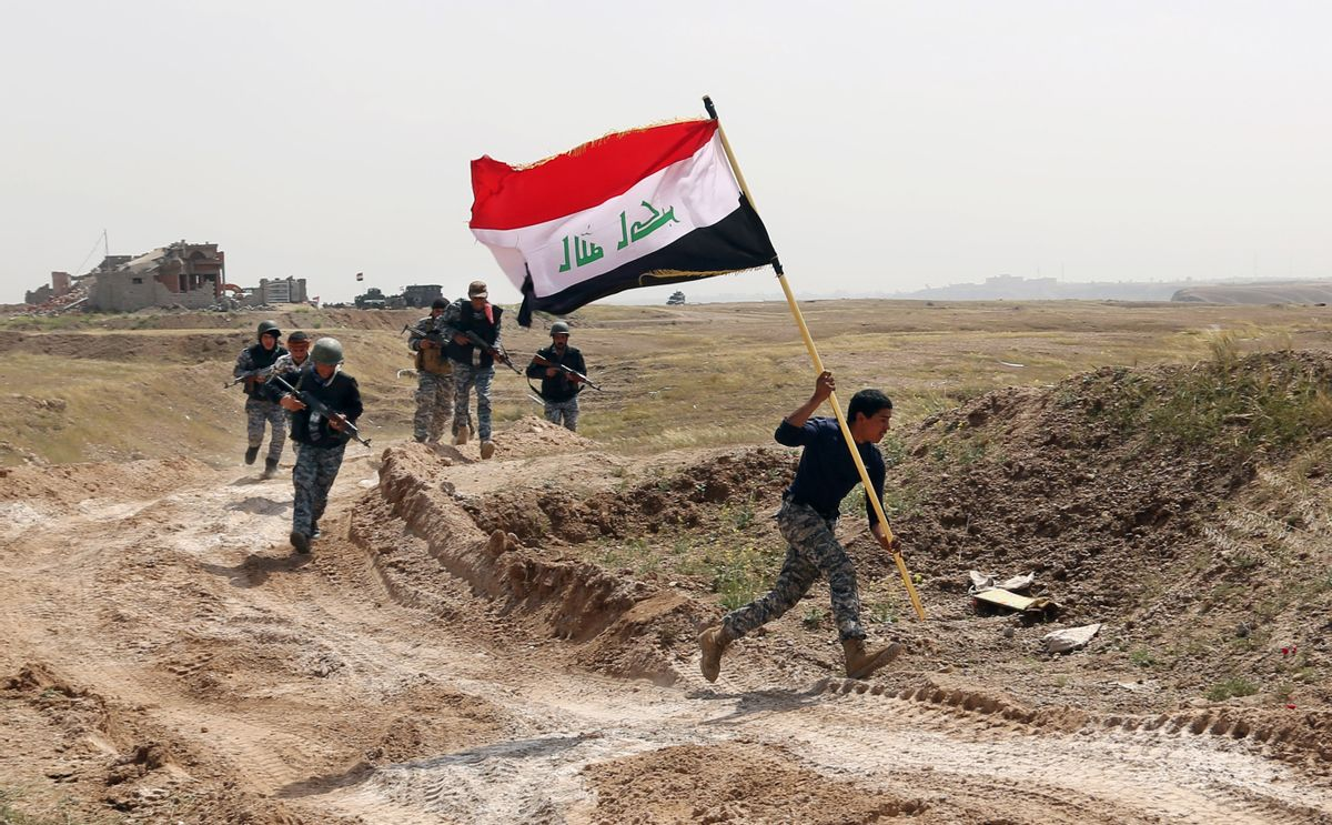 File - This Monday, March 30, 2015 file photo shows a member of the Iraqi security forces running to plant the national flag as they surround Tikrit during clashes to regain the city from Islamic State militants, 80 miles (130 kilometers) north of Baghdad, Iraq. (AP Photo/Khalid Mohammed, File) (AP)