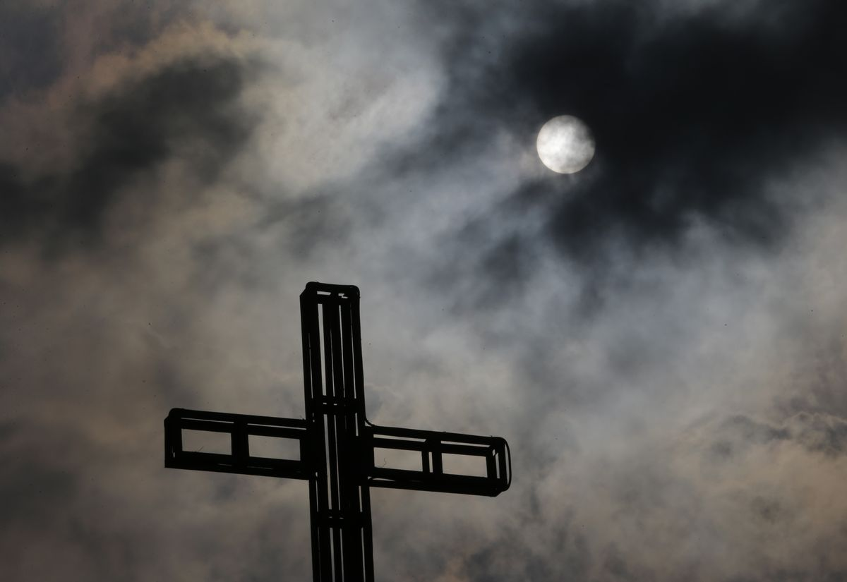 In this April 5, 2015, photo, dark clouds partially cover the sun above a church on Easter Sunday, north of Manila, Philippines. Tropical storm Maysak weakened before hitting the Philippines' northeastern coast Sunday, driving away thousands of Lenten holiday vacationers and tourists. (AP Photo/Aaron Favila, File) (AP)