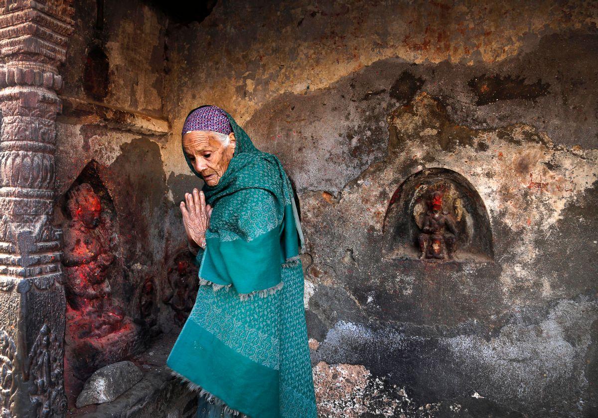 An elderly Nepalese woman prays at a damaged temple in earthquake , in Kathmandu, Nepal ,Friday, May 1, 2015. (AP Photo / Manish Swarup) (Manish Swarup)