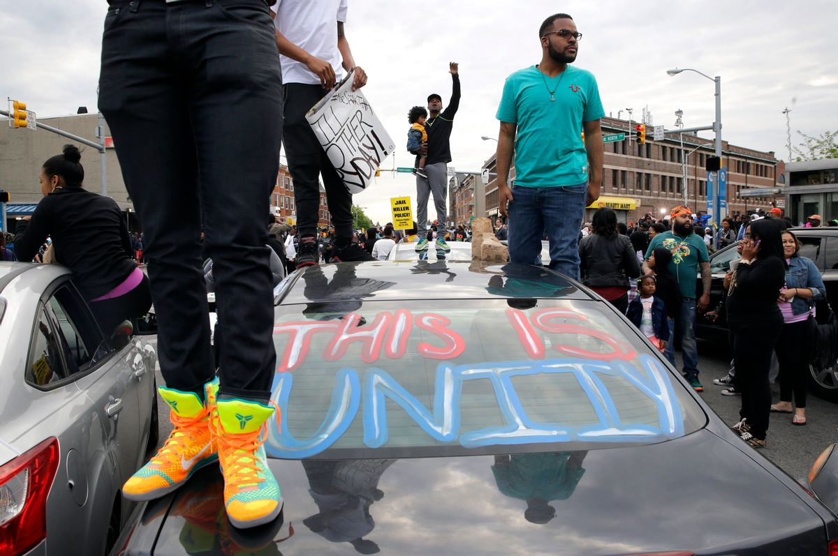 """Protesters stand on cars near the intersection of North Avenue and Pennsylvania Avenue in Baltimore, Friday, May 1, 2015, the day of the announcement of charges against the police officers involved in Freddie Gray's arrest. State's Attorney Marilyn Mosby announced the stiffest charge, second-degree """"depraved heart"""" murder, against the driver of the police van that Gray was in after his arrest. Other officers faced charges of involuntary manslaughter, assault and illegal arrest. (AP Photo/Patrick Semansky)  (AP)"""