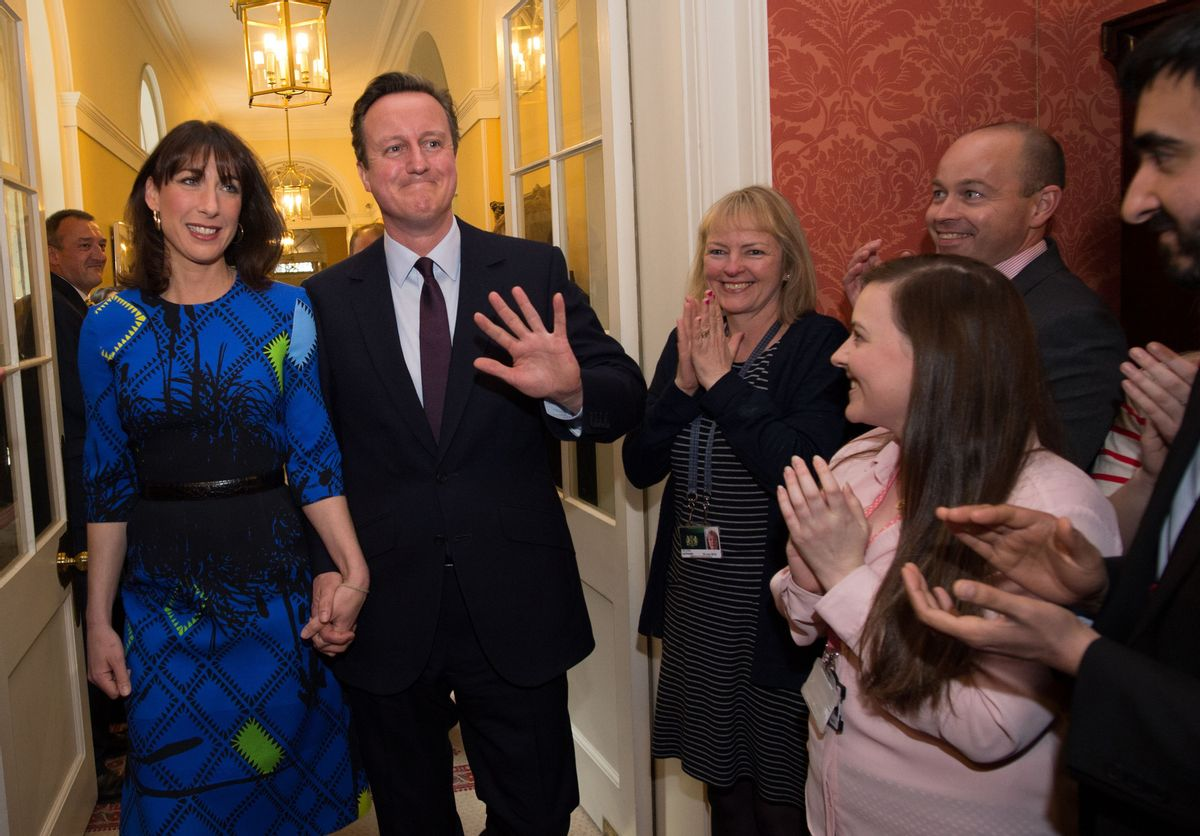 Britain's Prime Minister David Cameron and his wife Samantha are applauded by staff upon entering 10 Downing Street in London Friday May 8 2015, as he begins his second term as Prime Minister following the Conservative Party's win in Thursday's General Election . (Stefan Rousseau/Pool Photo via AP) (AP)