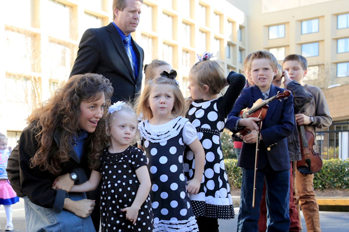 Michelle Duggar, kneeling, and Jim Bob Duggar, back right, and many of the Duggar's 19 children, in Raleigh, N.C., March 14, 2014.                   (AP/Ted Richardson)