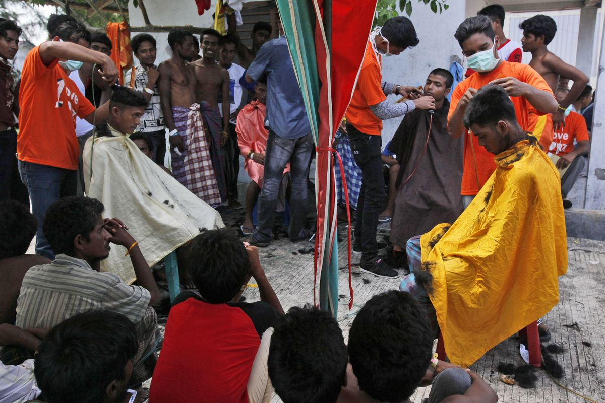 """Ethnic Rohingya men take free haircut service provided by a local NGO at a temporary shelter in Langsa, Aceh province, Indonesia, Tuesday, May 19, 2015.  Indonesia has """"given more than it should"""" to help hundreds of Rohingya and Bangladeshi migrants stranded on boats by human traffickers, its foreign minister said Tuesday, a day before she was to meet with her counterparts from the other countries feeling the brunt of the humanitarian crisis. (AP Photo/Binsar Bakkara) (Binsar Bakkara)"""
