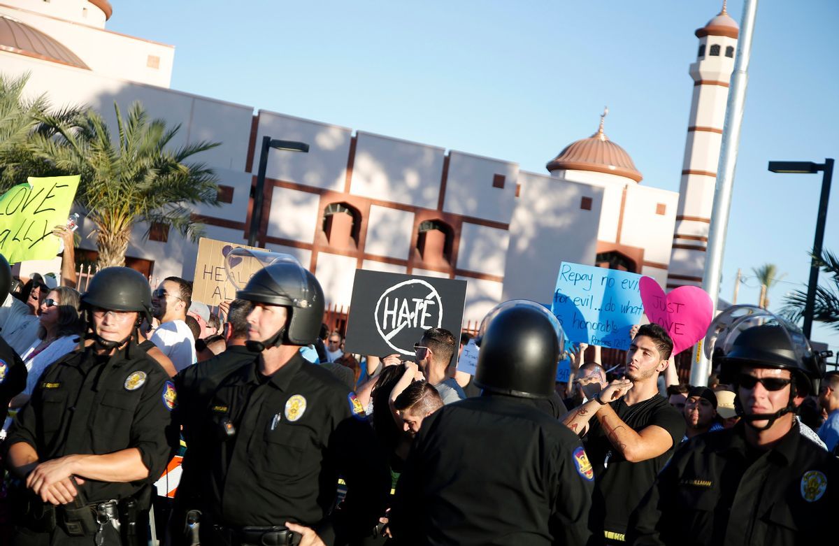 Protesters gather outside the Islamic Community Center of Phoenix, Friday, May 29, 2015. About 500 protesters gathered outside the Phoenix mosque on Friday as police kept two groups sparring about Islam far apart from each other.  (AP Photo/Rick Scuteri) (AP)