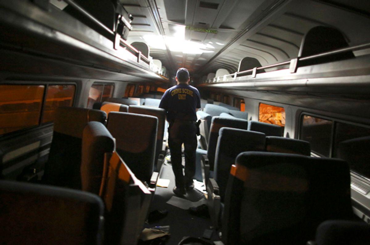 A crime scene investigator looks inside a train car after a train wreck, Tuesday, May 12, 2015, in Philadelphia.        (AP/Joseph Kaczmarek)
