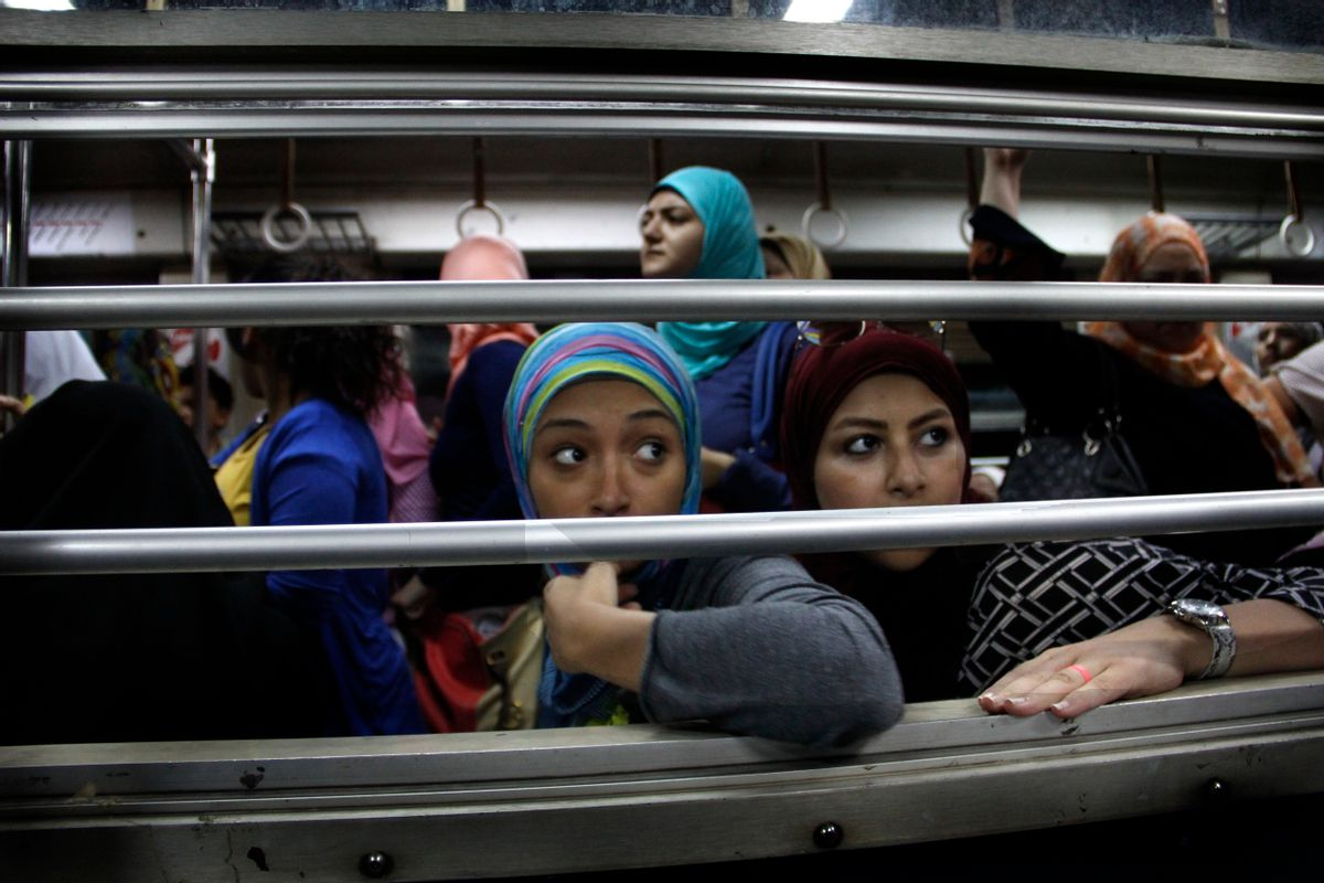 In this Sept. 13, 2014 photo, Egyptian women look from an all-female car at the Shohadaa (Martyrs) metro station in Cairo, Egypt. Before the 2011 Egyptian revolution the station was named for former President Hosni Mubarak. In a city known, as much as anything, for its dysfunction, the Cairo Metro stands as a singular achievement. It's reliable, well-maintained and relatively clean. (AP Photo/Heba Elkholy) (AP)