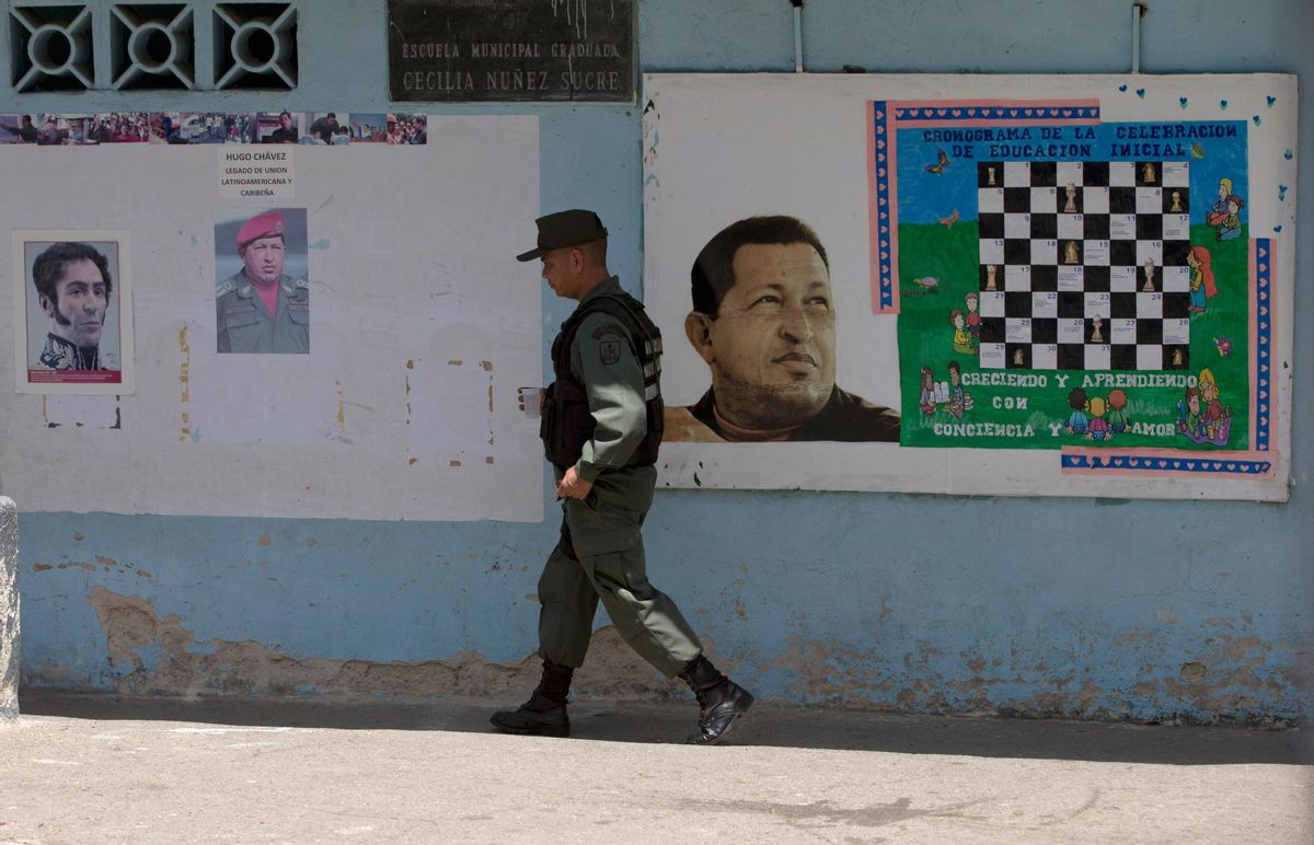 A Bolivarian National Guards officer walks near images of the late Venezuelan President Hugo Chavez and Independence hero Simon Bolivar, left, at a poll station in Caracas, Venezuela, Sunday, May 17, 2015. Venezuelans are voting to select the opposition leaders who will run against the ruling socialist party's candidates in upcoming legislative elections thought to be government critics' first chance at an electoral victory in years. (AP Photo/Fernando Llano) (AP)