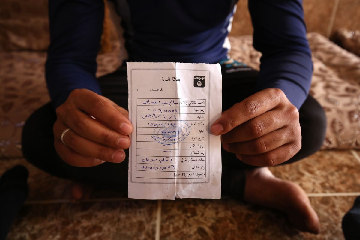 """In this Wednesday, May 27, 2015 photo, Salim Ahmed, a former Iraqi Army member, holds the """"repentance card"""" he received from the Islamic State group in June 2014 shortly after the militants took over his home village of Eski Mosul in northern Iraq. The document is part of the apparatus of control the Islamic State group has constructed across its self-declared """"caliphate,"""" the territory it conquered in Syria and Iraq. (AP Photo/Bram Janssen) (AP)"""