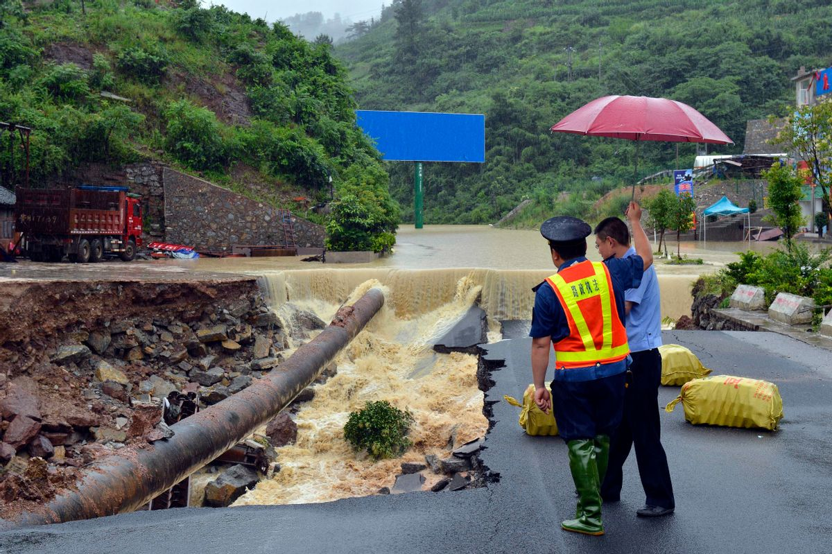 In this Thursday, June 18, 2015 photo, government officials look at a road that collapsed due to flooding in Kaili city in southwestern China's Guizhou province. Heavy storms that swept through several southern Chinese provinces this past week have killed 18 people and left four more missing, according to the Ministry of Civil Affairs. (Chinatopix Via AP) CHINA OUT (AP)