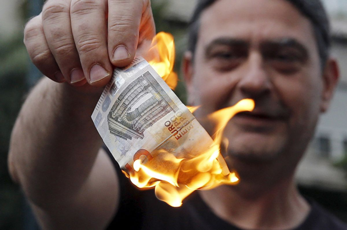 Anti-austerity protesters burn a euro note during a demonstration outside the European Union (EU) offices in Athens, Greece June 28, 2015.     (Reuters/Alkis Konstantinidis)