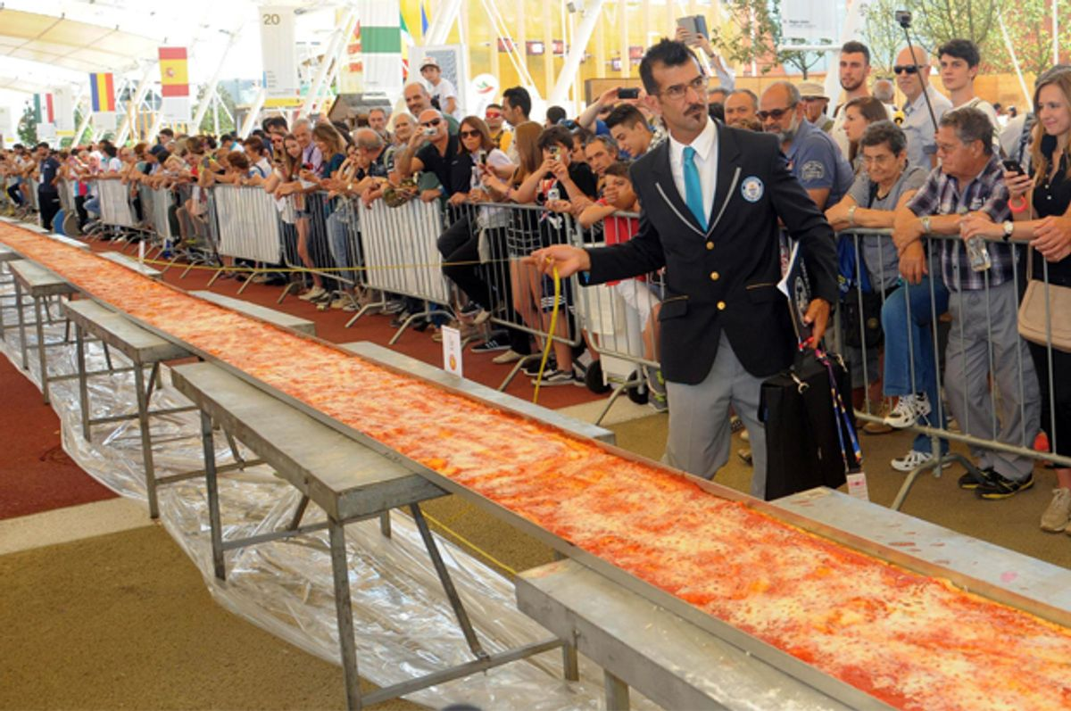 Judge of the Guinness World Records Lorenzo Veltri checks the length of a pizza at the Expo 2015 world's fair in Rho, near Milan, June 20, 2015.          (AP/Daniele Mascolo)