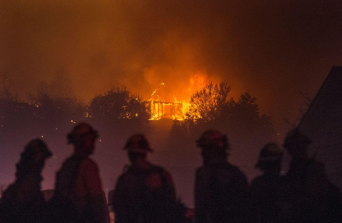 In this Sunday, June 28, 2015 photo provided by The Wenatchee World, Forest Service fire fighters from Leavenworth  watch as a house burns in northern Wenatchee, Wash. A wildfire fueled by high temperatures and strong winds roared into a central Washington neighborhood, destroying properties and forcing residents of several hundred homes to flee, authorities said Monday. (Don Seabrook/The Wenatchee World via AP)  (AP)