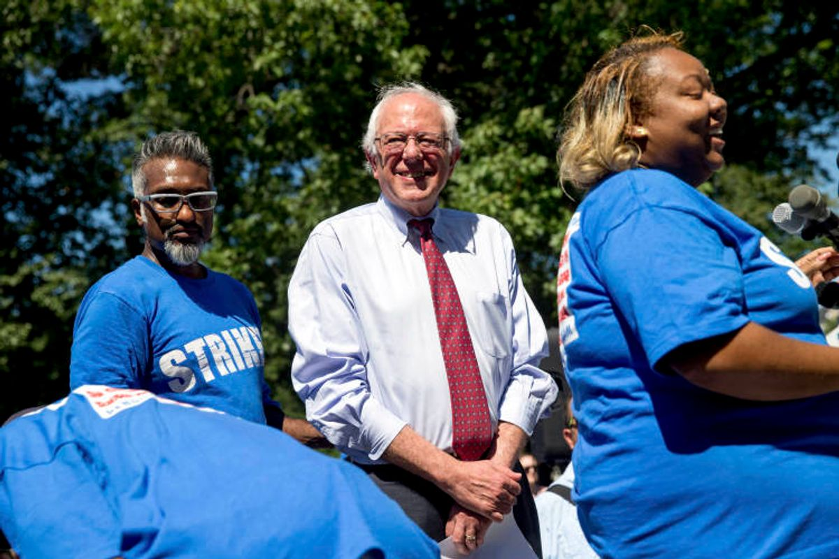 Democratic presidential candidate Sen. Bernie Sanders, I-Vt., center, joins federal contract workers to speak during a rally on Capitol Hill in Washington, Wednesday, July 22, 2015, to push for a raise to the minimum wage to $15 an hour. (AP Photo/Andrew Harnik) (AP)