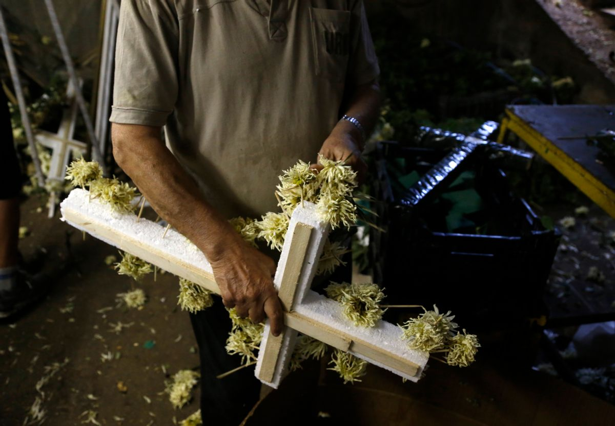 A worker removes the flowers from a wreath in Athens, Friday, July 17, 2015. Funeral homes here are struggling to cope with banking restrictions _ with a modest funeral costing more the 15 times the daily ATM withdrawal limit _ in a country that traditionally carries out funerals shortly after death and almost everything is paid for in cash. (AP Photo/Petros Karadjias) (AP)