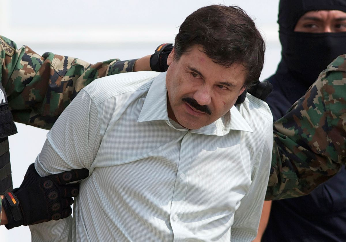 """In this Feb. 22, 2014, file photo, Joaquin """"El Chapo"""" Guzman, head of Mexico's Sinaloa Cartel, is escorted to a helicopter in Mexico City, following his capture. He escaped and was caught again on Friday. (AP)"""