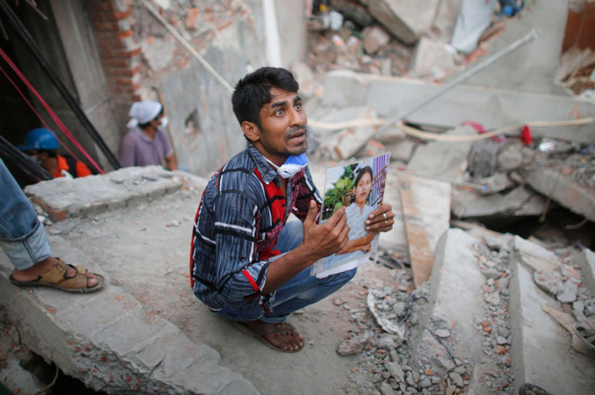 A relative holds up a picture of a garment worker in front of the rubble of the collapsed Rana Plaza building, in Savar, April 27, 2013.           (Reuters/Andrew Biraj)