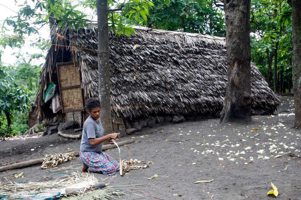 A woman weaves a mat in a village on Tanna Island in Vanuatu on Tuesday, June 2, 2015. Tanna Island was particularly hard hit by Cyclone Pam, which struck in March. Many people in Vanuatu believe the cyclone was the latest manifestation of climate change. (AP Photo/Nick Perry) (Nick Perry)