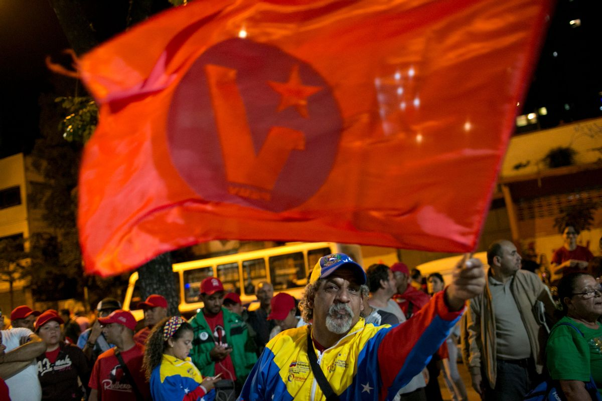 Pro-government supporters, one waiving a ruling party flag, demand that a polling station reopen after its official closing, during congressional elections in Caracas, Venezuela, Sunday, Dec. 6, 2015. Some members of the opposition are angry after elections officials ordered polling centers to stay open for an extra hour, even if no one was standing in line to vote. Government opponents mobbed some voting stations demanding that the National Guard stick to the original schedule of closing at 6 p.m. (AP Photo/Alejandro Cegarra) (AP)