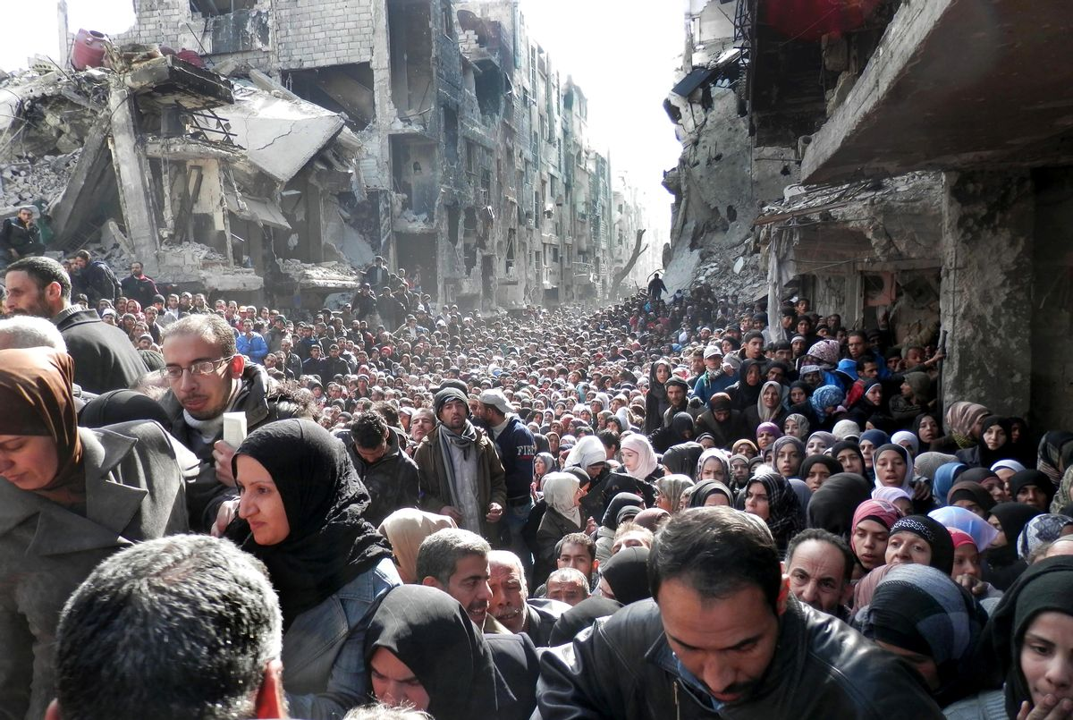FILE - In this Jan. 31, 2014 file photo released by the United Nations Relief and Works Agency for Palestine Refugees in the Near East (UNRWA), shows residents of the besieged Palestinian camp of Yarmouk, queuing to receive food supplies, in Damascus, Syria. That year, the U.N. was able to deliver food to about five percent of people in besieged areas including Yarmouk, while today estimates show the organization is reaching less than one percent.(UNRWA via AP, File) (AP)