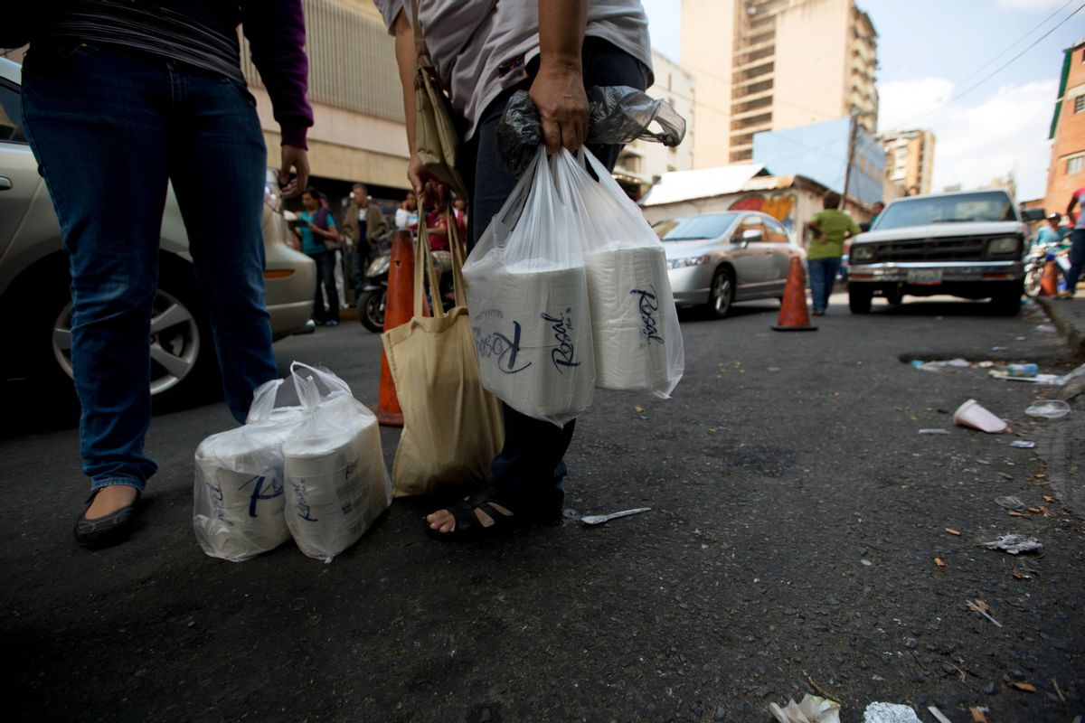 After waiting in line for hours, women stand outside a supermarket in Caracas, Venezuela, with their price regulated toilet paper made available for sale by the government, Friday, Jan. 22, 2016. In a note published Friday, the International Monetary Fund Western Hemisphere Director Alejandro Werner said inflation would more than double in the economically struggling South American country in 2016, reaching 720 percent. (AP Photo/Fernando Llano) (AP)
