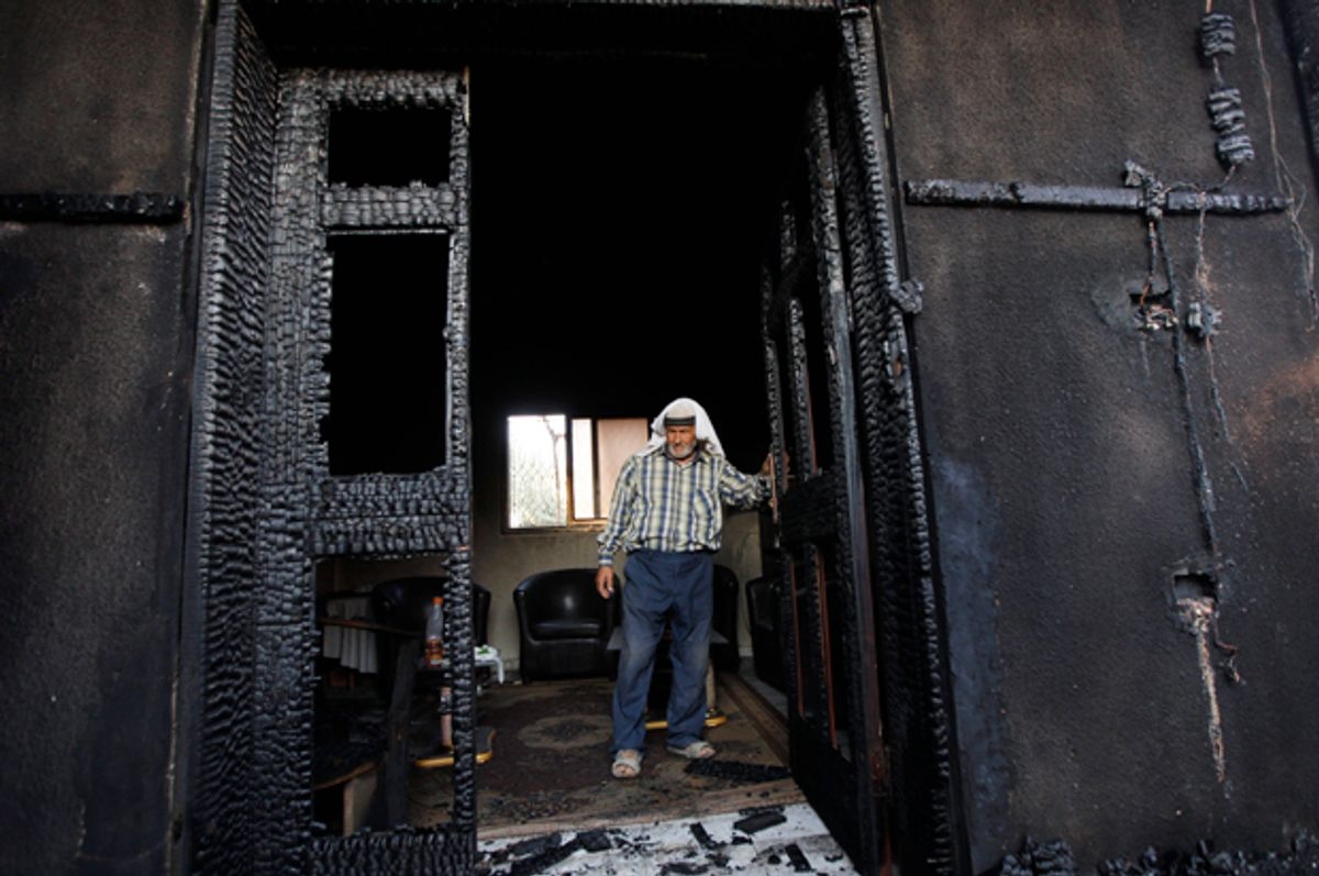A Palestinian inspects a house after it was torched in a suspected attack by Jewish settlers, killing an 18-month-old Palestinian child and his parents, at Duma village near the West Bank city of Nablus. (AP/Majdi Mohammed)