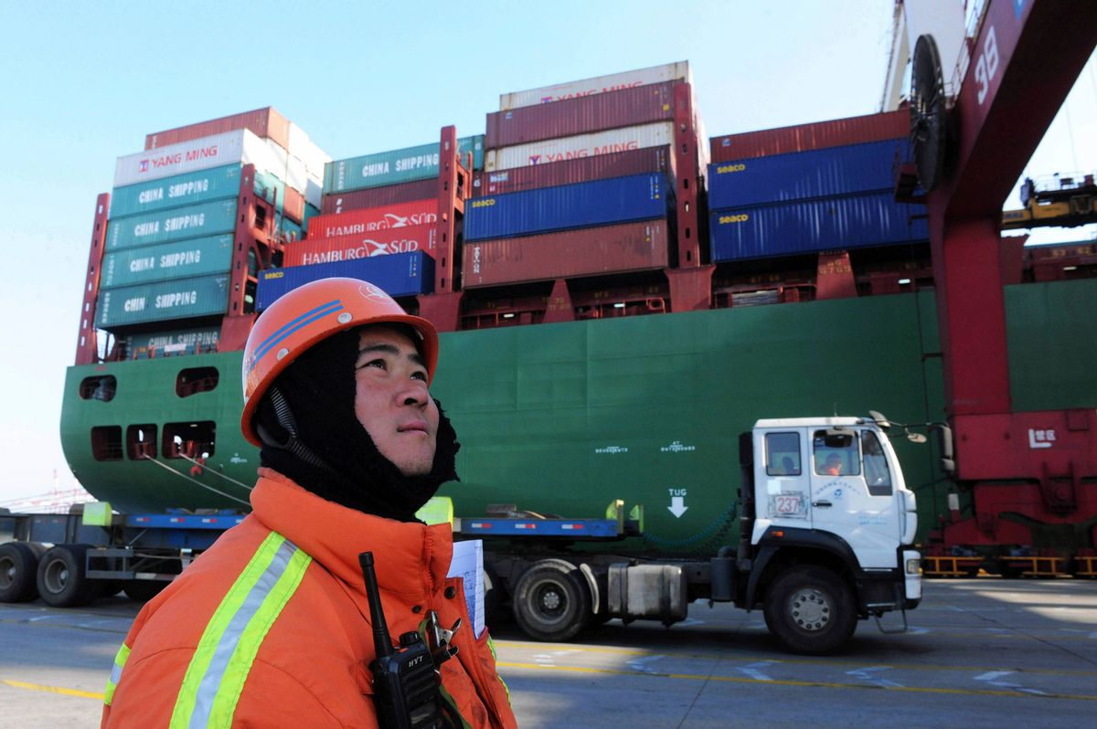 A port worker stands near a container ship at a port in Qingdao in eastern China's Shandong province Monday Feb. 15, 2016.  (Chinatopix Via APCHINA OUT)