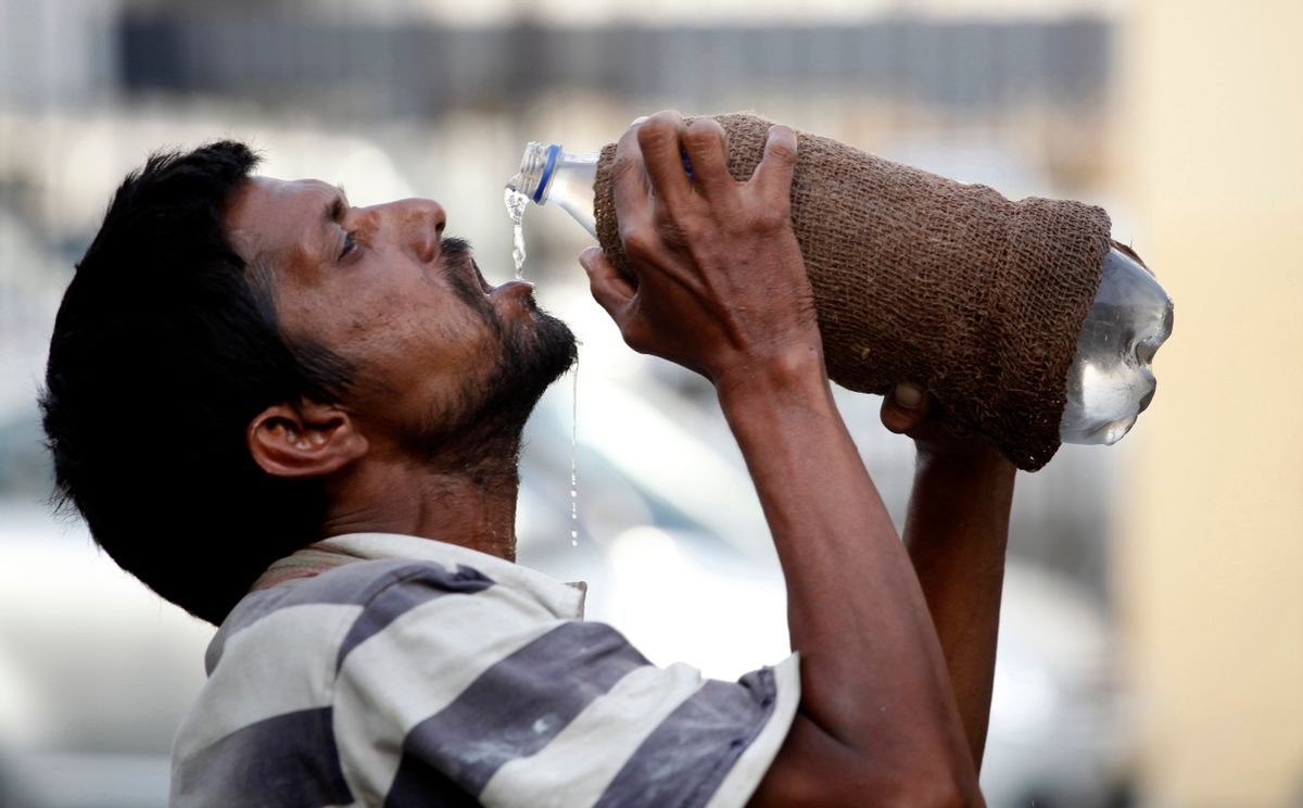 FILE - In this Sunday, May 31, 2015, file photo, an Indian drinks water from a bottle on a hot summer day in Allahabad, India. India is launching programs to protect people from extreme heat in two high-risk cities, after a devastating heat wave killed at least 2,500 people across the country last year. (AP/Rajesh Kumar Singh, file)