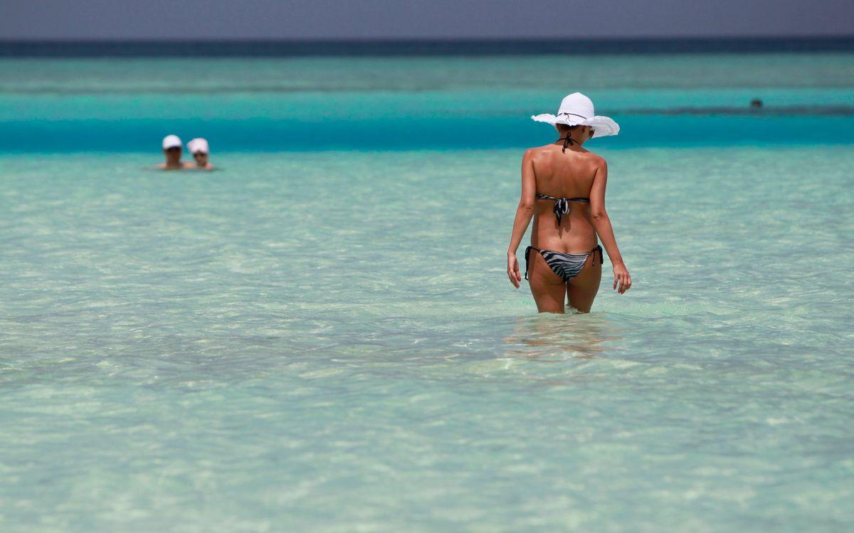 FILE- In this Feb. 14, 2012 file photo, a tourist walks in the shallow lagoon of Paradise island resort in Male atoll, Maldives.(AP Photo/ Gemunu Amarasinghe, File) (AP)