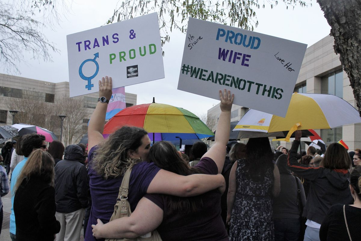 Two protesters hold up signs against passage of legislation in North Carolina, which limits the bathroom options for transgender people, during a rally in Charlotte, N.C., Thursday, March 31, 2016. The rally drew around 100 people at the Charlotte-Mecklenburg Government Center. (AP Photos/Skip Foreman) (AP)