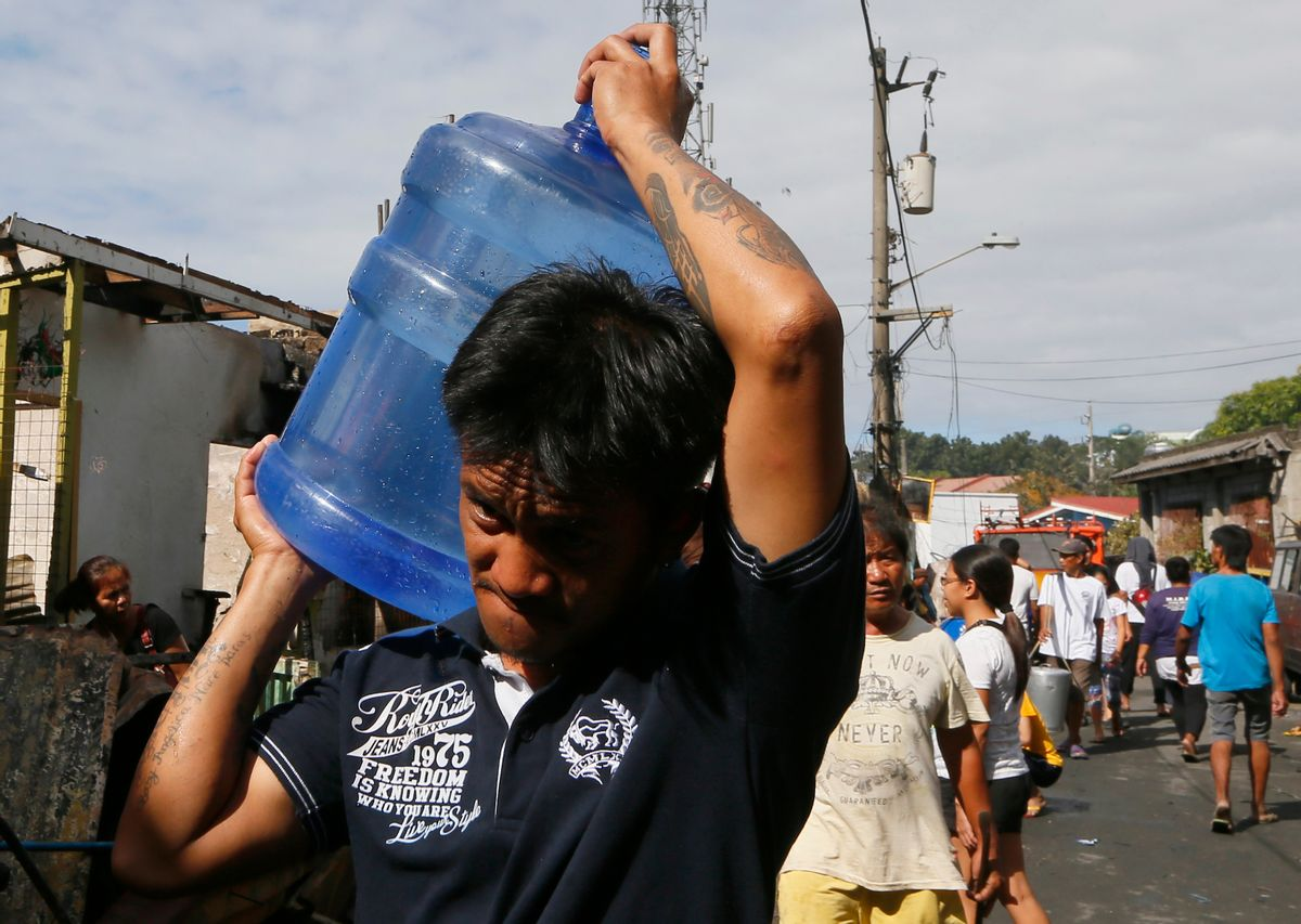 """In this Feb. 23, 2016 photo, a resident carries drinking water following an overnight fire at a poor neighborhood in Muntinlupa city southeast of Manila, Philippines. Water was not supposed to become so expensive for Manila under a 1997 World Bank deal that privatized the seaside city's water and sewage management. That arrangement is under fire by the U.S. congressional committee that oversees the international development bank, which is now questioning whether the World Bank and its lending arm, the International Finance Corp., should join in such """"public-private partnerships.""""  (AP Photo/Bullit Marquez) (AP)"""