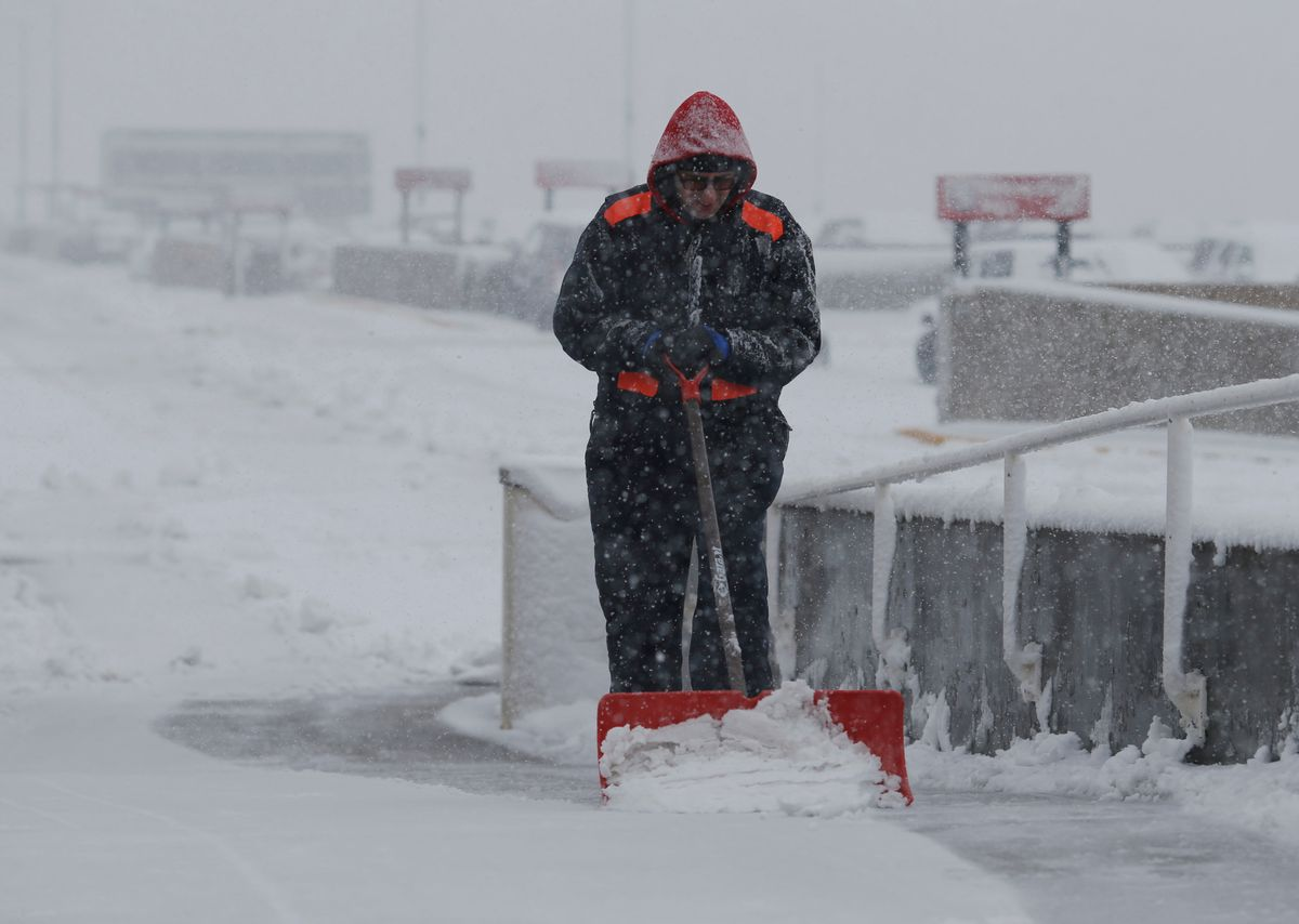 An unidentified maintenance man clears snow from a walkway at Denver International Airport as a severe spring storm packing high winds and heavy, wet snow sweeps over the intermountain West forcing the cancellation of hundreds of flights, Saturday, April 16, 2016, in Denver. (AP Photo/David Zalubowski) (AP)