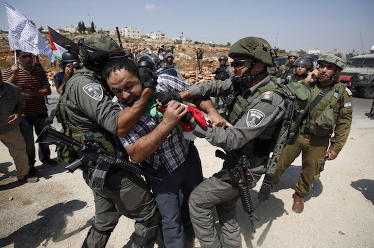 Israeli forces detain a Palestinian protester during a demonstration against illegal Israeli settlements in the occupied West Bank village of Nabi Saleh, near Ramallah on September 4, 2015  (Reuters/Mohamad Torokman)