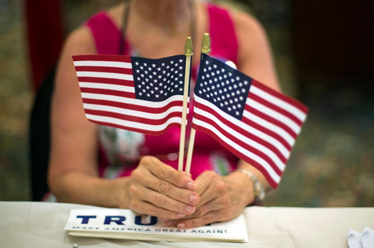 A volunteer hands out flags at a Donald Trump Rally in Bluffton, S.C., July 21, 2015.    (AP/Stephen B. Morton)