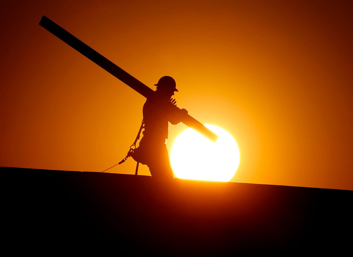 A home builder works at sunrise, Monday, June 20, 2016, in Gilbert, Ariz., in an effort to beat the rising temperatures. (AP Photo/Matt York)