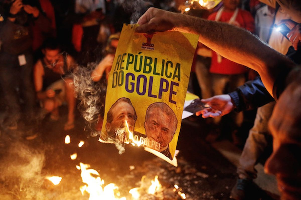 """Brazilian activists burn a poster reading """"Republic of the Coup,"""" with the images of Senate President Renan Calheiros (L) and right-wing interim President Michel Temer, at a protest in Sao Paulo, Brazil on May 12, 2016  (Reuters/Nacho Doce)"""
