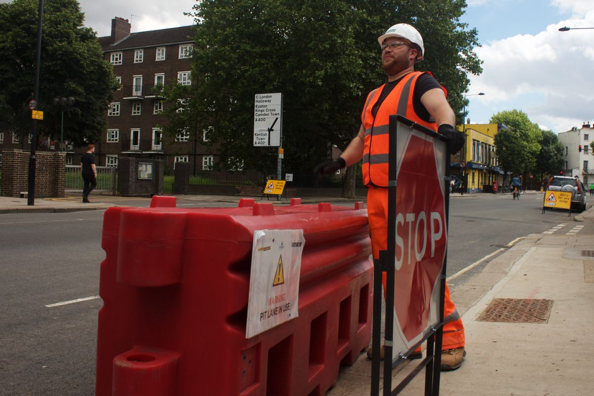 In this photo taken on Friday, June 24, 2016, Gabriel Ionut, a 24-year-old Romanian who works as a traffic marshal, stands by a signal at a construction site in London. (AP Photo, Pawel Kuczynski)